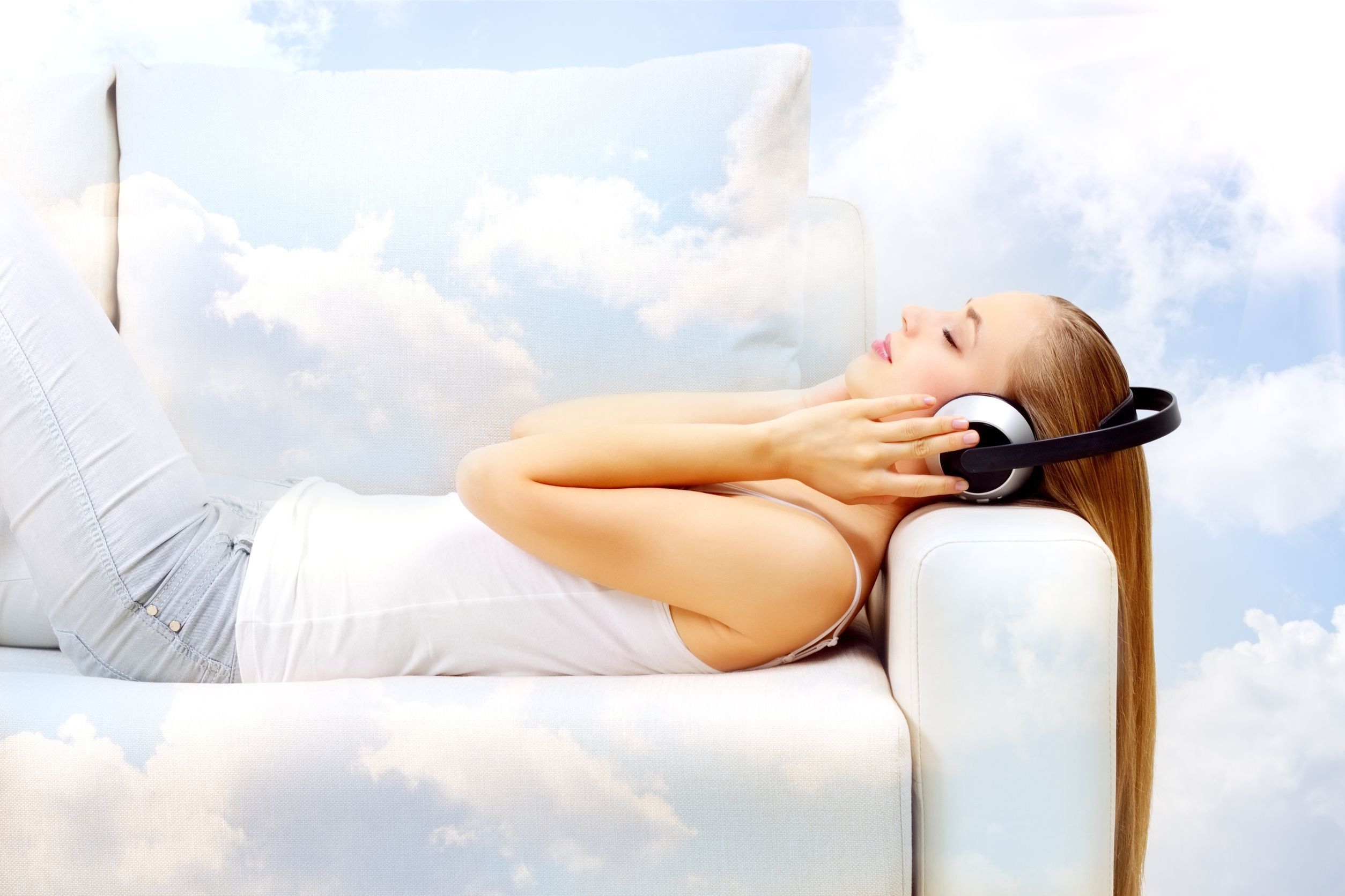 12589398 - young attractive girl lying on sofa, listening to music in the clouds