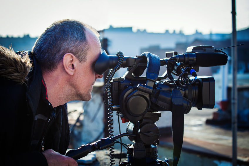 cameraman with his video camera shooting outdoor in the city on roofs